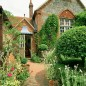 Brick garden footpath leading to country house with plants and pots