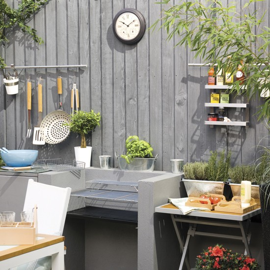 Kitchen Garden With Concrete Barbecue And Grey Fence