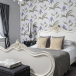 White French bed and patterned wallpaper