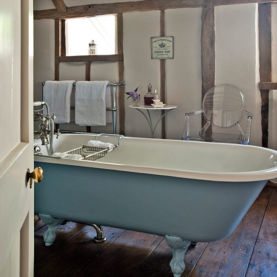 Bathroom with blue freestanding bath floorboards and exposed beams