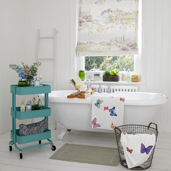 White bathroom with printed blind and green storage unit