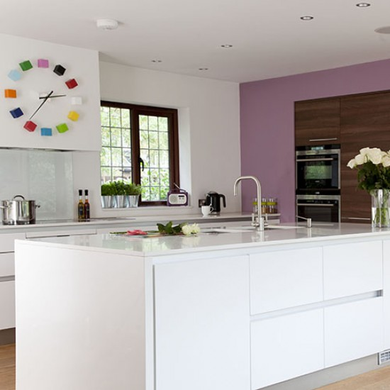 White Kitchen With Lilac Feature Wall And Bright Clock