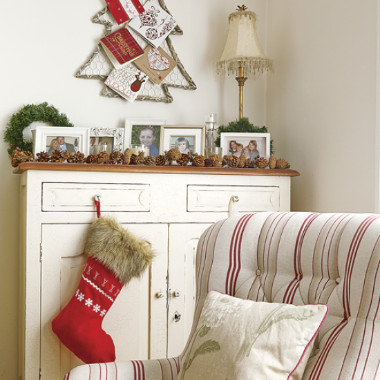 Country Christmas living room with Christmas tree card holder, white console, striped armchair and red stocking