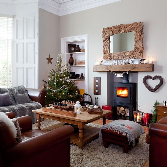 Country Christmas living room with neutral walls, wood flooring, neutral shag pile rug, wood coffee table, leather sofas, wood mirror frame and Christmas tree