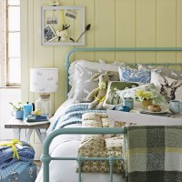 Yellow country bedroom with teal bedstead