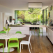Open-plan kitchen with wood floor, handless white cabinetry, stainless steel worktop, marble table and green plastic chairs