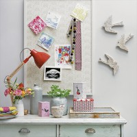 Grey home office with distressed desk and wallpapered pinboard