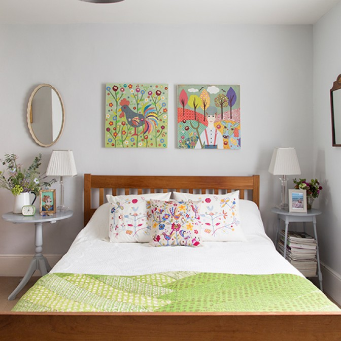 White bedroom with folksy artworks and cushions