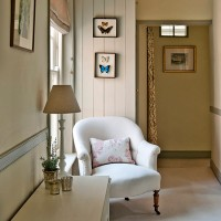 Cream country hallway with armchair and butterfly pictures