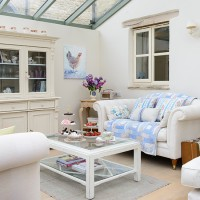 Neutral conservatory with white sofa and coffee table