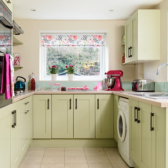 Kitchen With Green Painted Units And Floral Blind