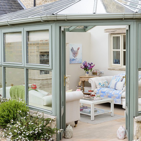 Green Country Conservatory With White Walls And Wooden Flooring