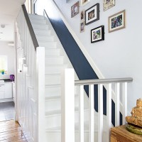 Classic hallway with painted staircase and family photographs
