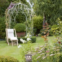 Garden with rose arch and country planting