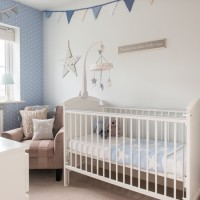 Pale blue and taupe nursery with polka-dot wallpaper