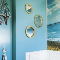 Blue bathroom with port-hole mirrors and seascape wall
