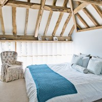 Country-style beamed bedroom with duck-egg painted walls