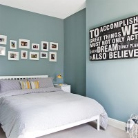 Blue bedroom with white bed and photograph display