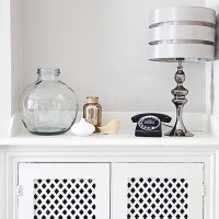 White hallway with storage cupboard and lamp