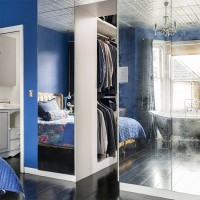 Bright blue bedroom with mirrored walk-in wardrobe