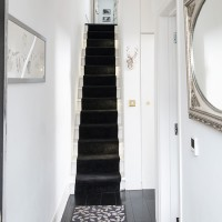 Narrow period hallway with black stair runner