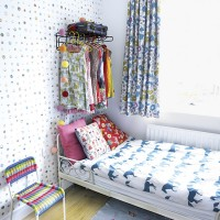 Modern bedroom with patterned wallpaper and motif bed linen