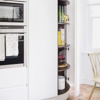 White kitchen with rounded larder and terracotta flooring