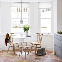 White classic dining room with stone flooring and sash windows