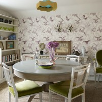 Country dining room with patterned wallpaper and round dining table and chairs