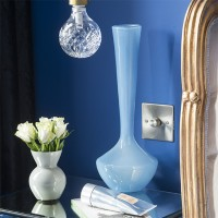 Blue and white glass vases on a mirrored bedside table