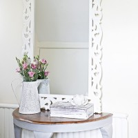 Carved white mirror frame on hall console table