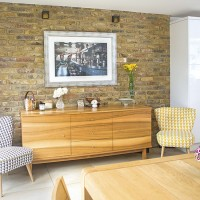 Modern Scandi-style dining area with exposed brick wall