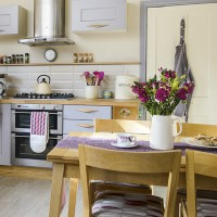Vintage-style kitchen with lilac units and retro wooden handles