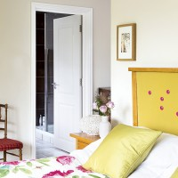 White traditional bedroom with yellow headboard and floral duvet