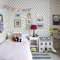 Children's bedroom with rose print wallpaper and bunting