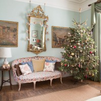 Traditional blue living room with Christmas tree and ornate mirror