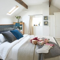 White loft bedroom with cosy bedlinen and skylight