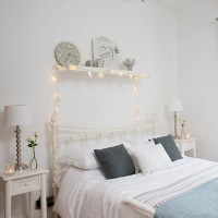 White bedroom with metal bedstead and fairy lights