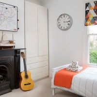 Child's white bedroom with orange accents