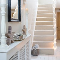 White and bright hallway staircase with Christmas lights