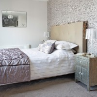 Contemporary double bedroom with upholstered headboard and rectangular wall mirror