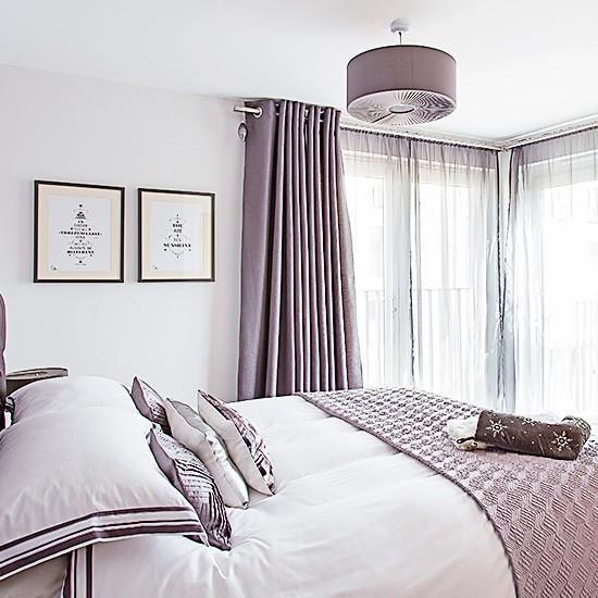 bedroom with corner window and mauve bedspread