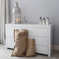 White sideboard with three drawers and large candle lantern on top