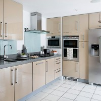 Pale modern kitchen units with glass splashbacks and white tiled floors