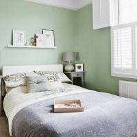 Pale green bedroom with white shutters and wall art
