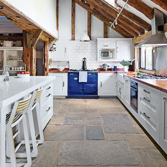 Rustic kitchen with blue aga and impressive flagstone for Country kitchen floor ideas