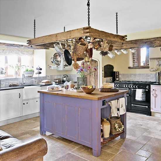 Rustic kitchen with ceiling-hung pan rack and purple island