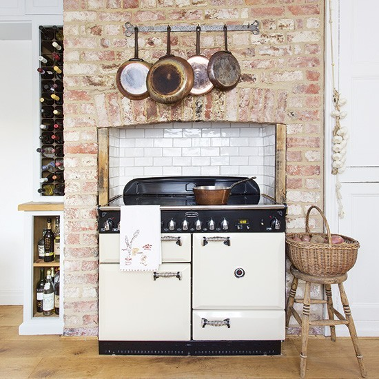 Rustic kitchen with white Aga in exposed-brick chimney