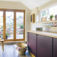 Neutral kitchen with purple cabinetry and wooden worktops
