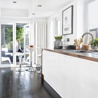 White modern kitchen with handleless units and dark wood floor